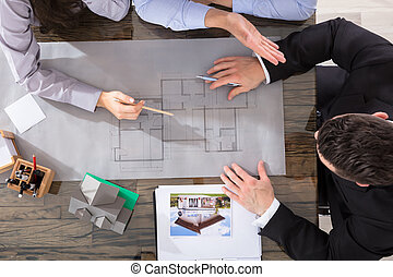 Couple And Architect Working On Blueprint