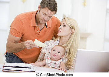 Couple and baby in dining room with laptop and paperwork