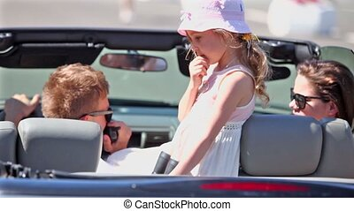 couple and girl sit in cabriolet, boy talk by hand radio
