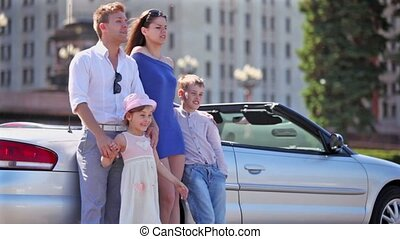 couple and kids stand near cabriolet, boy hold girl - Young...