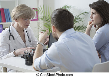 Young infertile couple on medical consultation with female gynecologist