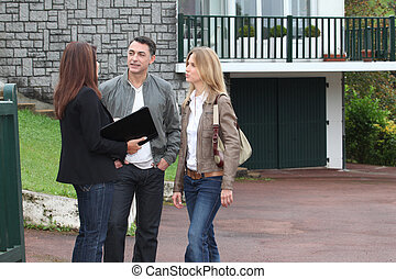 Couple and real-estate agent in front of house for sale