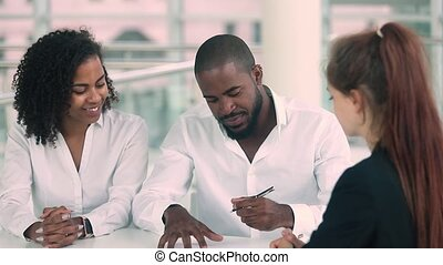 Couple and realtor after signing rental agreement handshakes...