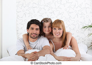 couple and their little girl in bed