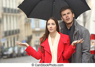 Couple annoyed in a rainy day