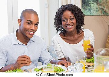 couple, apprécier, repas sain, sourire, appareil photo, ensemble