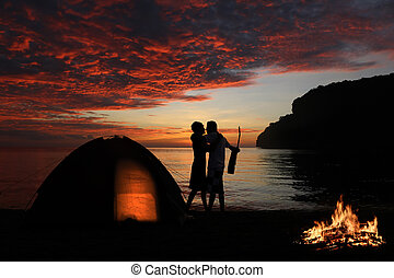 Couple are kissing and camping with campfire on the beach