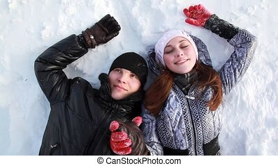 Couple are lying on the snow holding hands