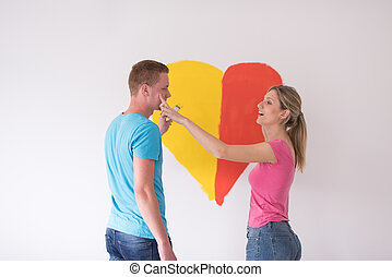 couple are painting a heart on the wall