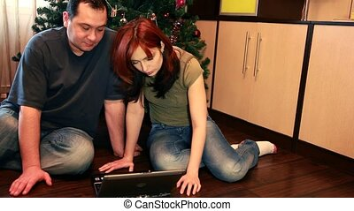 Couple are sitting on the floor considering notebook