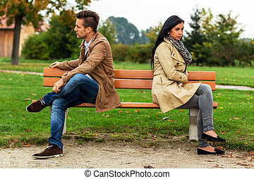 couple arguing - a young couple sitting on a park bench and...