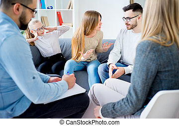 Couple arguing at therapy session in therapists office