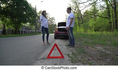 Couple arguing in front of broken down car on quiet country ...
