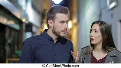 Couple arguing in the night in the street