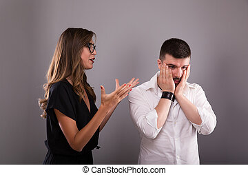 Couple arguing. Young woman speaking emotionally, blaming man, gesturing, explaining opinion. Unhappy girlfriend shouting to frustrated boyfriend, guy sitting back not talking to her.