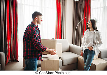 Couple arrange boxes, moving to new house