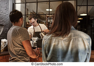 Couple at a cafe counter with barista pouring coffee