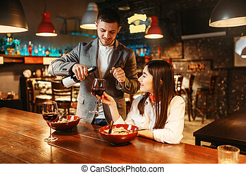 Couple at bar counter, romantic date celebration