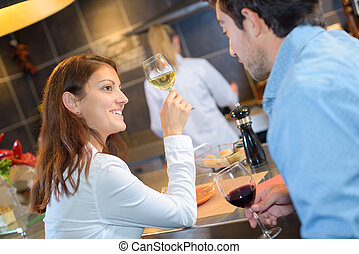 Couple at bar holding glasses of wine