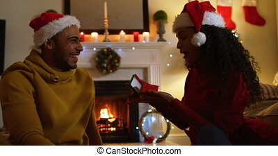 Side view close up of a mixed race couple in their sitting room at Christmas, wearing santa hats and sitting together on the floor, the woman opening a present from the man, both laughing