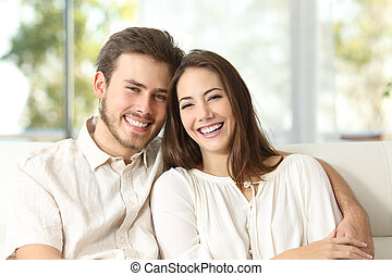 Couple at home looking at camera - Happy couple sitting on a...
