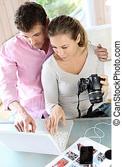 Couple at home looking at pictures on camera and laptop