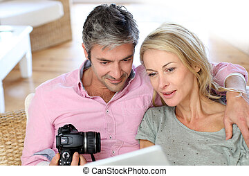 Couple at home looking at pictures on electronic tablet
