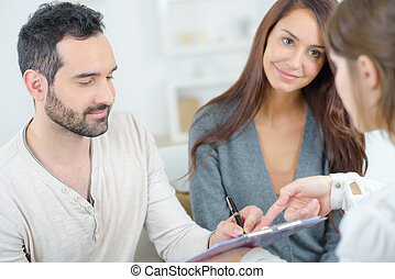 couple at home signing paper