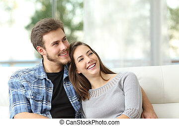Happy couple thinking and looking sideways sitting on a couch at home