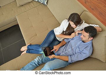 couple at home using tablet computer