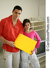 Couple at home with a blank board