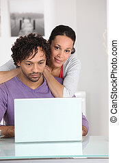 Couple at home with a laptop computer