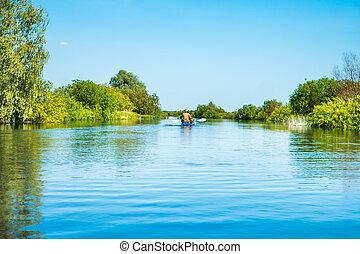 Couple at kayak trip on blue river landscape