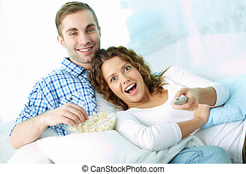 Couple at leisure - Portrait of young couple watching TV at...