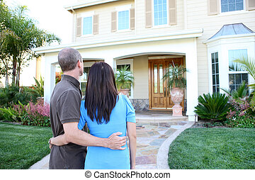 Couple at New Home - An attractive happy couple in front of...
