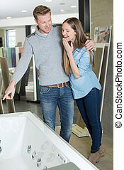 couple at plumbing store choosing bath