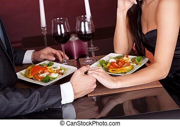 Lovely young couple having romantic dinner in restaurant