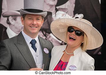 Couple at Royal Ascot laughing at camera - A man in grey ...