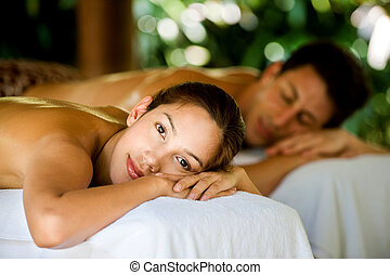 An attractive young couple lying on massage beds at a spa outdoors