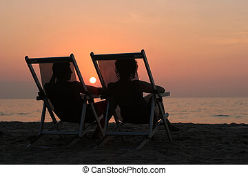 Couple sitting in the chairs watching sunset at the beach