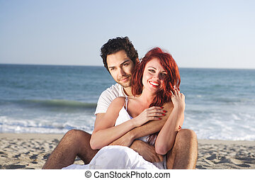 Couple at the beach seducing each other