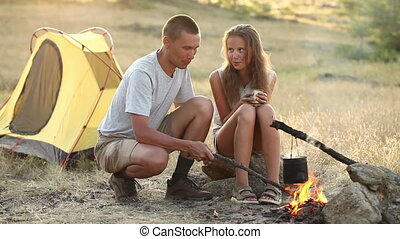 Couple at the camping with campfire in a sunny summer day