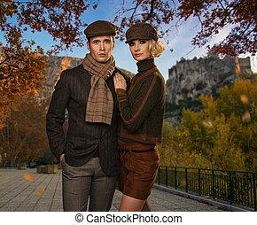 couple, automnal, contre, casquettes, élégant, paysage