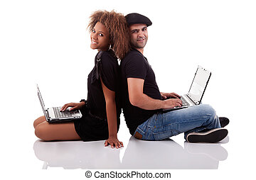 Couple back to back, sitting on the floor, with computers, isolated on white background, studio shot