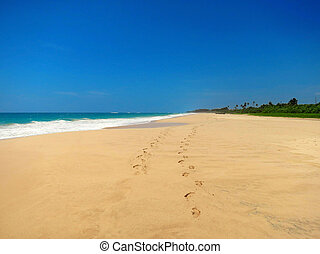 Couple barefoot at empty sandy beach, Koggala, Sri Lanka