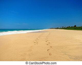 Couple barefoot at empty sandy beach, Koggala, Sri Lanka