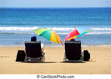 Couple beach - A couple relaxing on a beach under colorful...