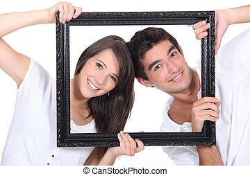 couple behind black frame