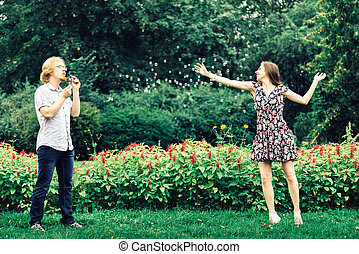Couple blowing bubbles outdoor