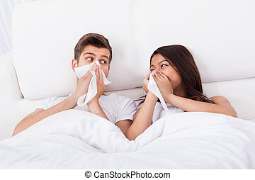 Couple Blowing Their Noses At Home - Young couple looking at...